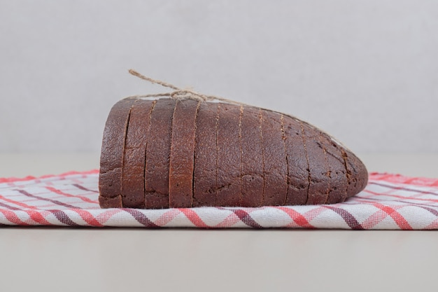 Gesneden vers bruin brood in touw op tafellaken. hoge kwaliteit foto