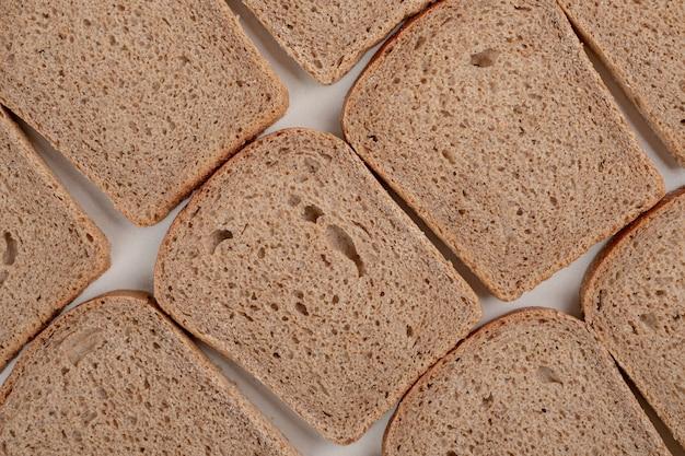 Gesneden vers bruin brood op witte ondergrond
