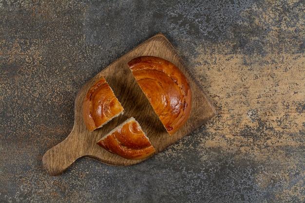 Gesneden vers gebak op een houten bord.