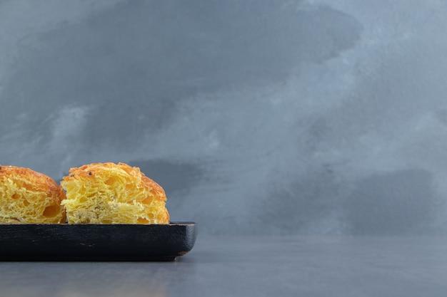 Gesneden vers gebak op zwarte plaat.