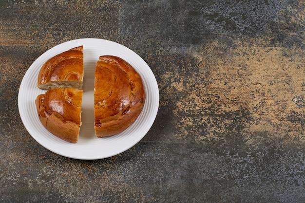 Gesneden vers gebakje op witte plaat.