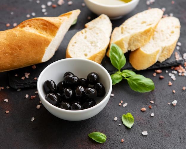 Gesneden vers knapperig stokbrood met olijf en kruiden