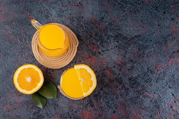 Gesneden vers oranje fruit met bladeren en een glaswaterkruik sap dat op steenlijst wordt geplaatst.
