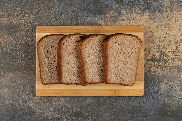 Gesneden vers roggebrood op een houten bord