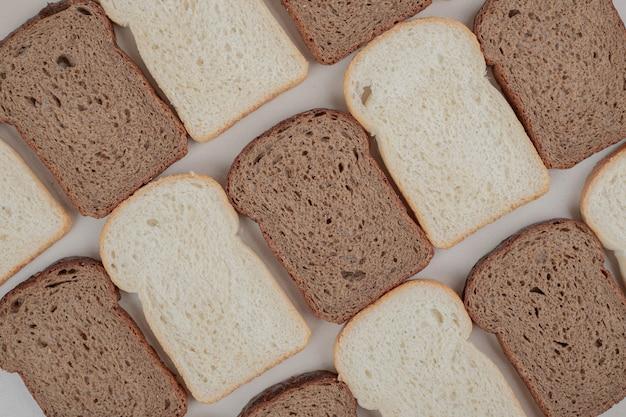 Gesneden vers wit en bruin brood op wit oppervlak