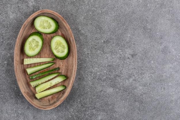 Gesneden verse biologische komkommer in houten kom over grijs oppervlak.