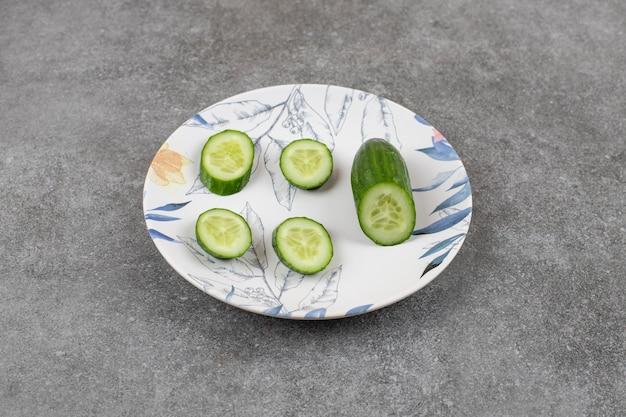 Gesneden verse biologische komkommer op witte plaat.