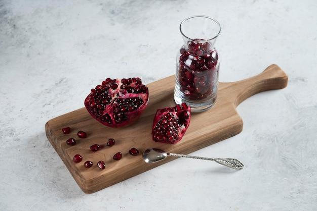 Gesneden verse granaatappel met een kruik op een houten bord.