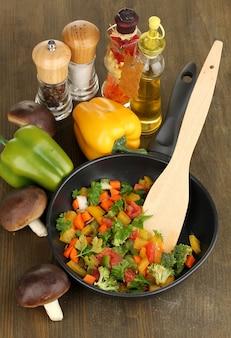 Gesneden verse groenten in pan met kruiden en ingrediënten op houten tafel