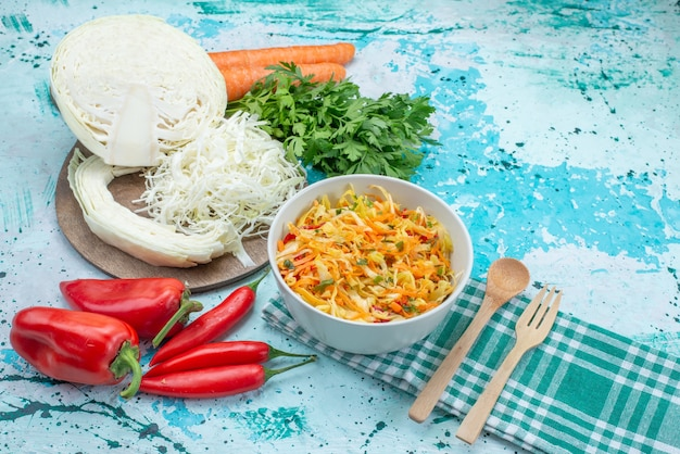Gesneden verse groenten lange en dunne plakjes salade binnen plaat met greens kool paprika op blauw
