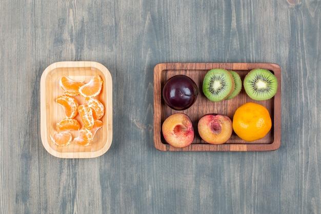 Gesneden verse kiwi met sinaasappel en pruimen op een houten bord
