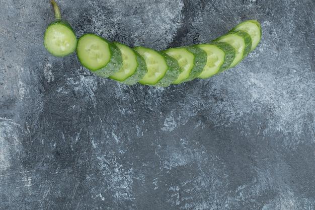 Gesneden verse komkommer op grijze achtergrond.