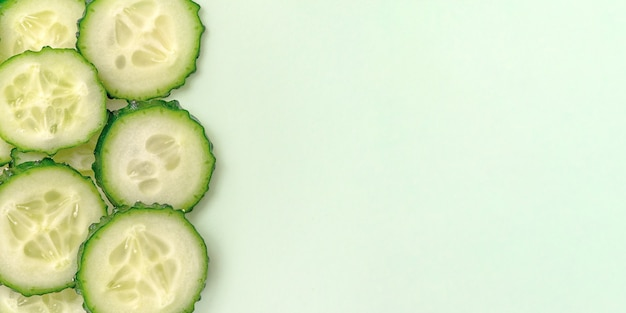 Gesneden verse komkommer op lichtgrijs. bovenaanzicht.