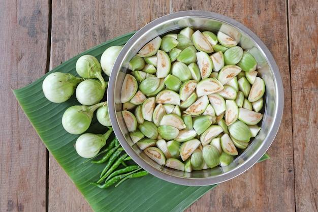 Gesneden verse organische aubergine in water en groene spaanse pepers op banaanblad tegen houten lijst