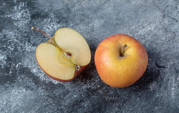 Gesneden verse rode appel op een marmeren achtergrond.