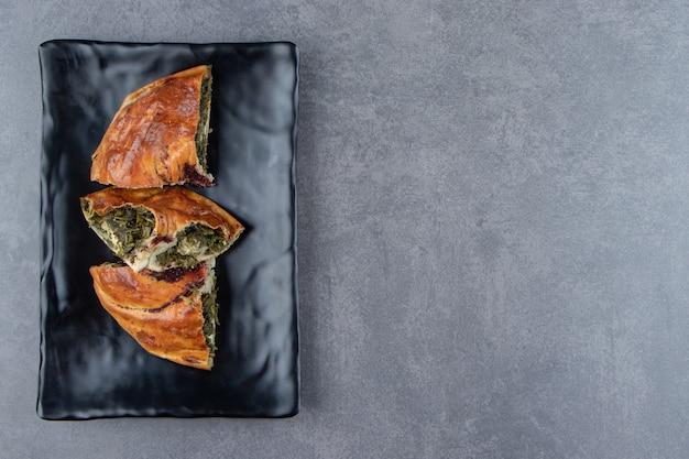 Gesneden verse taart met groenen op zwarte plaat.