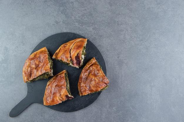 Gesneden verse taart met groenen op zwarte snijplank.