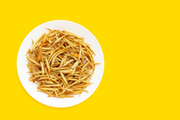 Gesneden vingerwortel op witte plaat op gele achtergrond.