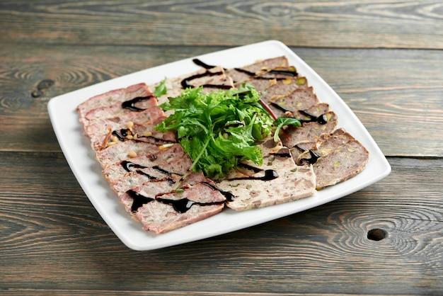 Gesneden vlees plaat versierd met greens en saus op de houten tafel in het plaatselijke restaurant copyspace eten voorgerecht gebakken delicatesse gastronomische hongerige eetlust concept.