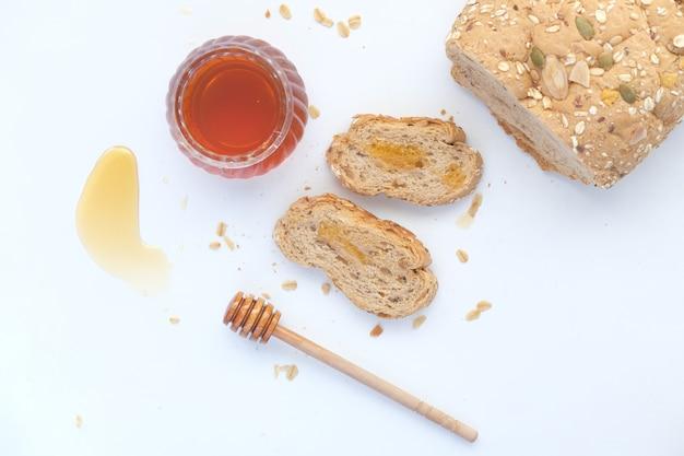 Gesneden volkoren brood met havervlokken en honing op wit