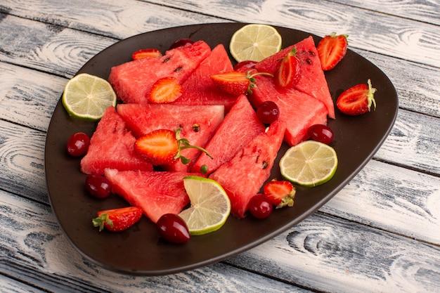 Gesneden watermeloen met citroenaardbeien in bruine plaat op grijs