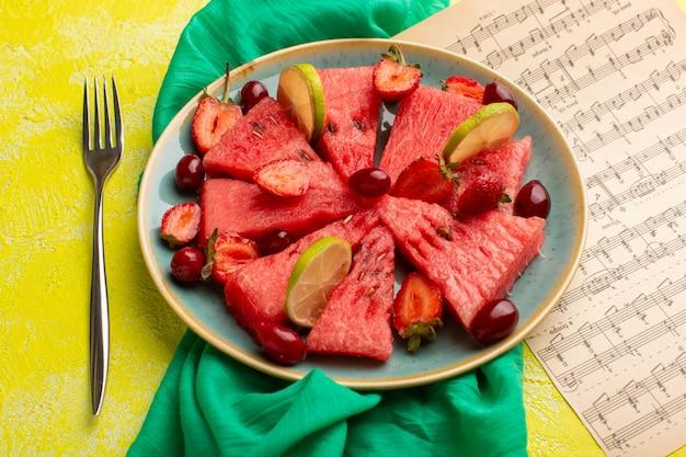 Gesneden watermeloen met citroenaardbeien op geel