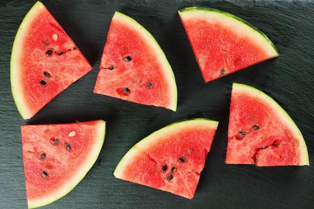 Gesneden watermeloen op zwarte leisteen oppervlak bovenaanzicht