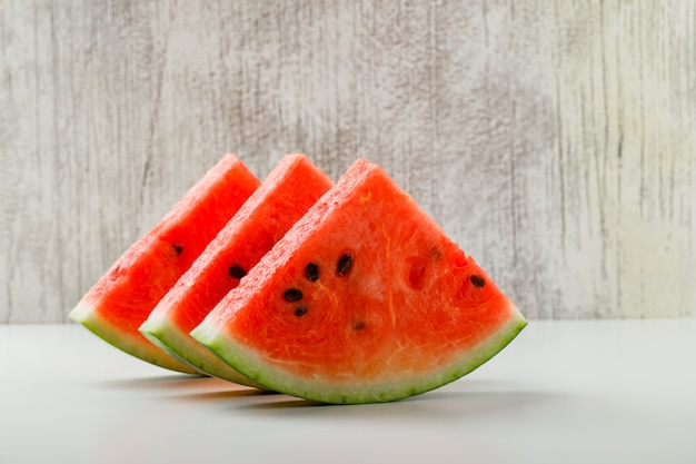 Gesneden watermeloen zijaanzicht over wit en grunge achtergrond