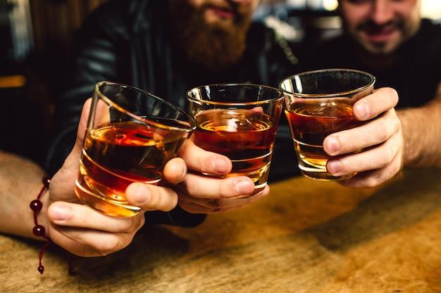 Gesneden weergave van drie bebaarde jonge mannen die glazen met rum bij elkaar houden. ze lachen. mensen zitten in de bar.