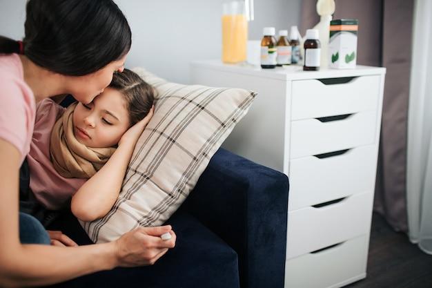 Gesneden weergave van jonge vrouw kussen voorhoofd van haar dochter. ze zit naast haar bank. ziek meisje dat daar ligt. moeder houdt thermometer in de hand. ze zijn in één kamer.