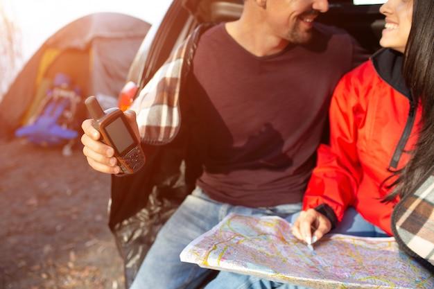Gesneden weergave van mooie paar zitten samen in kofferbak en glimlach. hij heeft een satelliettelefoon. ze heeft een kaart. mensen staan dicht bij tent.