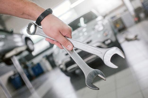 Gesneden weergave van sterke man's hand met twee sleutels voor witte auto. het grijze voertuig staat op het platform. er is een klok om de pols.