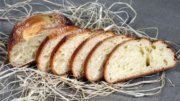 Gesneden witbrood liggend in stro op grijs linnen tafelkleed. granen eten
