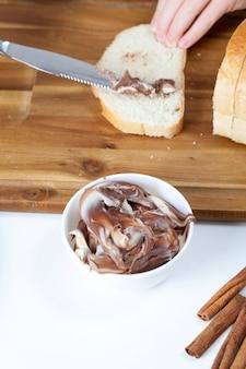 Gesneden witbrood met gesmeerde chocoladeboter, heerlijke chocoladeboter en witbrood, natuurlijke chocoladepasta met cacao tijdens het ontbijt