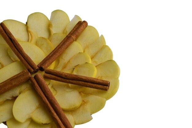 Gesneden witte appels en kaneel bekleed met een cirkel en een ster op een witte achtergrond