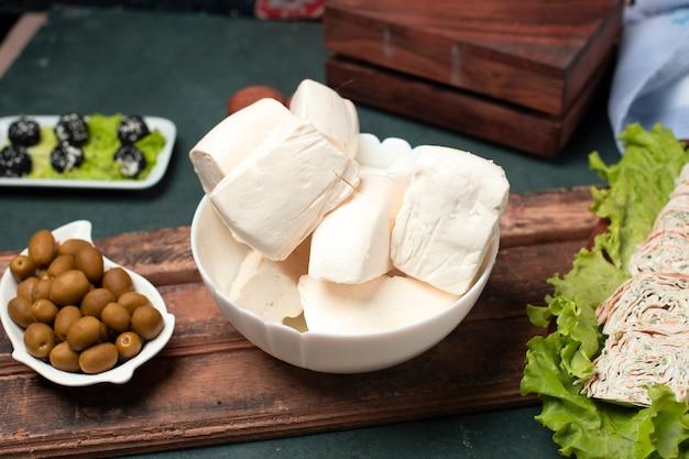 Gesneden witte kaas in een kom met groene olijven