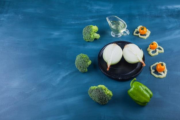 Gesneden witte radijs en groene broccoli op blauwe ondergrond.