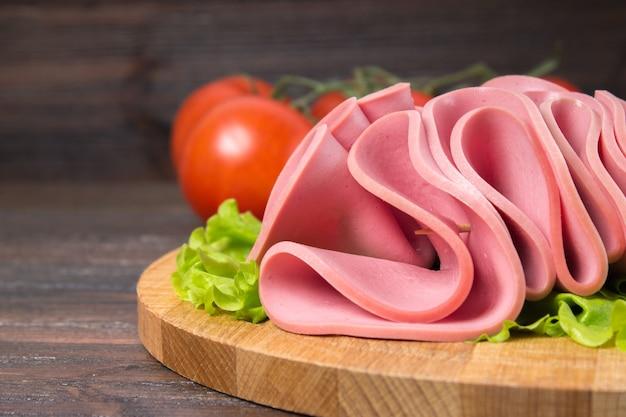Gesneden worsten met saladebladeren op de houten achtergrond