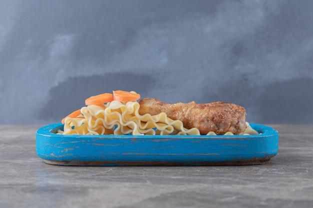 Gesneden wortel naast drumstick op de macarons op het blauwe dienblad, op het marmeren oppervlak.