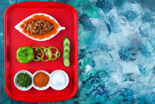 Gesneden wortelen en bonen en groenten op plaat op dienblad op blauw.
