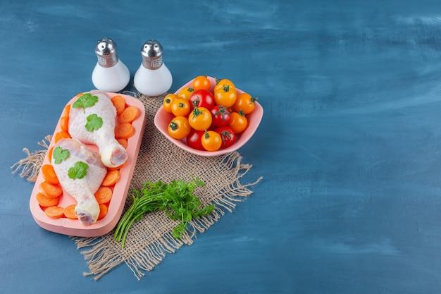 Gesneden wortelen en drumstick op een bord naast tomatenkom, op de blauwe achtergrond.