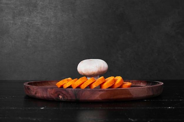 Gesneden wortelen en een paddestoel op een houten bord.