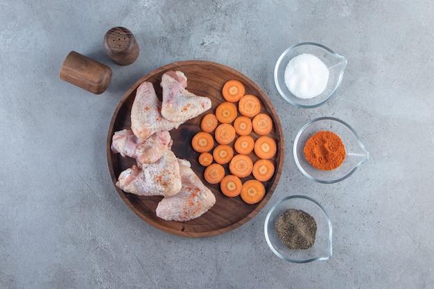 Gesneden wortelen en kippenvleugels op een houten bord naast kruidenkommen, op het marmeren oppervlak.