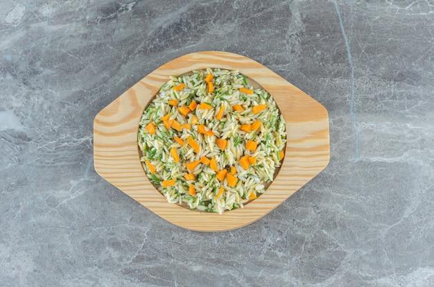 Gesneden wortelen en rijst op houten plaat, op de handdoek, op de marmeren tafel.