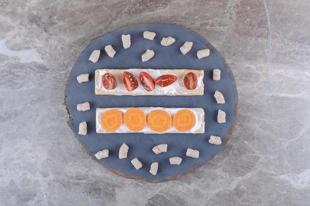 Gesneden wortelen en tomaten op knäckebröd, omgeven door kruimel op het bord, op het marmeren oppervlak