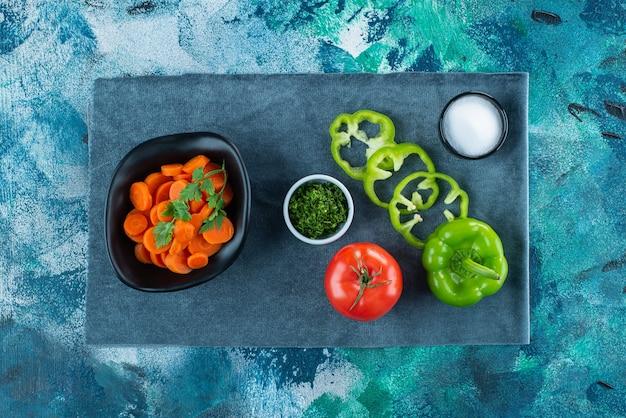 Gesneden wortelen in een kom naast groenten op handdoek op blauw.
