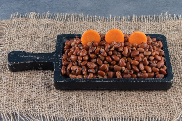 Gesneden wortelen op bonenbord op een jute-servet op het blauwe oppervlak