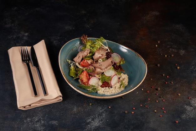 Gesneden zeldzame gebraden entrecote van rundvlees met geroosterde groenten op donkere achtergrond