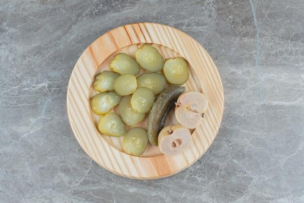 Gesneden zelfgemaakte augurk op houten plaat.