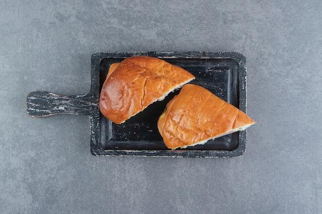 Gesneden zelfgemaakte gebak op zwarte snijplank.